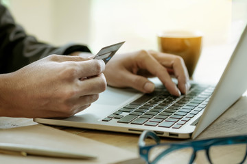 Online payment,Man's hands holding a credit card and using lapto