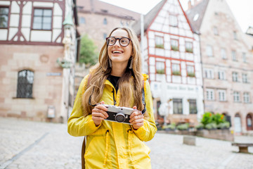 Young woman tourist in yellow raincoat standing with backpack on the old square with beautiful buildings on the background in Nurnberg city, Germany