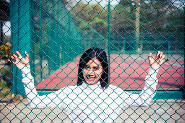 Portrait of asian woman on fence at tennis court