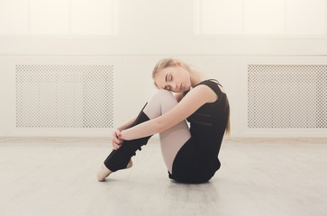 Classical ballet dancer stretching in white training class