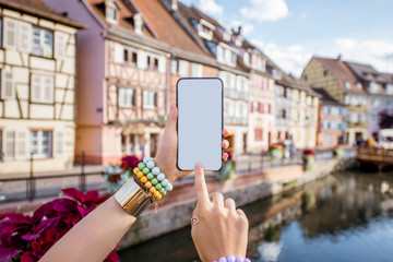 Woman holding phone on the old buildings background in Colmar village in Alsace in north-eastern France