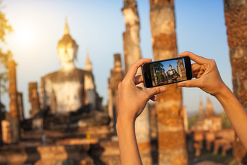 A hand taking photo of Buddha statue with smartphone, Sukhothai, Thailand