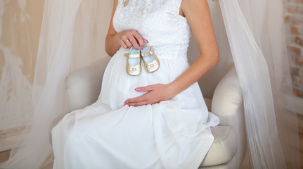 young pregnant girl sits on a beige chair and holds small golden baby shoes on background of the pregnant belly.