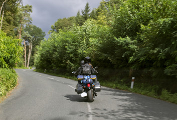 Young couple of motorcyclists riding on forest road. Active lifestyle. Europe trip.