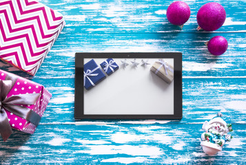 New year's background on a blue and white desk decorated with toys, presents, Christmas tree. Bright colored background symbolizes the new year celebration. Great useful template with a tablet.