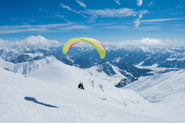 Zelfklevend Fotobehang Luchtsport Paraglider flying between the jagged snowy peaks