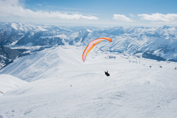 The sportsman on the paraglider makes a turn. flies over the snowy mountains