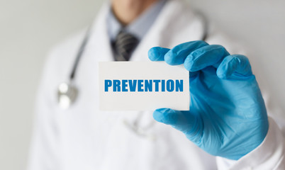 Doctor holding a card with text PREVENTION,medical concept