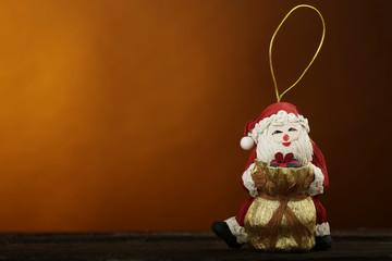 Pupazzetto decorativo di babbo natale da appendere all'albero su sfondo arancione