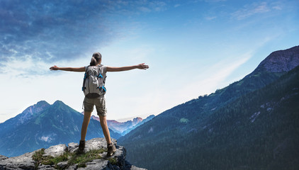 Happy woman with arms outstretched on rocky cliff