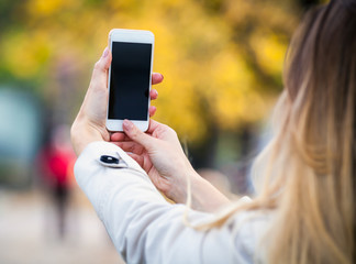 Woman taking picture with smartphone in colorful autumn street