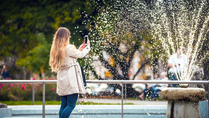 Woman in the autumn city taking picture of fountain on smartphone