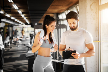 Young slim fitness girl standing with a towel near handsome trainer while showing her schedule for next week in the gym.