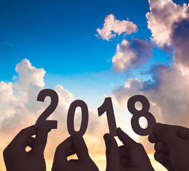 New year 2018,Silhouette hands holding Metal words of 2018 on sunset