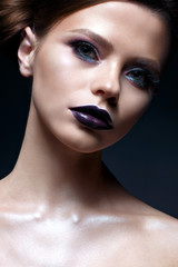 Young girl with creative makeup and hairdo. A beautiful model with bright eyes and purple lips. Shining skin. Beauty of the face. Photo taken in the studio