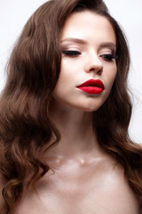 A young girl with a Hollywood wave and classic makeup. Beautiful model with red lips and arrows on eyes. Evening makeup and hairstyle. Beauty of the face.  White isolated background. Shining skin.