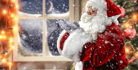 anta Claus blows snow from his hand. Great background with mountain view and Christmas tree with baubles.
