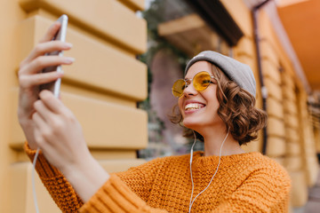 Lovely white girl with curly hairstyle making selfie in new outfit enjoying good weather. Outdoor portrait of ecstatic young woman in trendy sweater taking picture of herself beside old building.