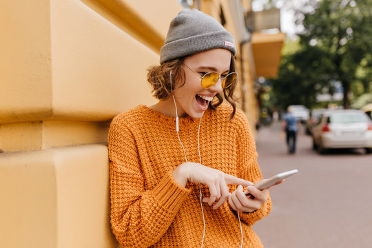 Glad girl in cozy outfit having fun outdoor waiting friend to walk together. Portrait of pretty female model in yellow sweater laughing while checking mobile mail on blur street background.
