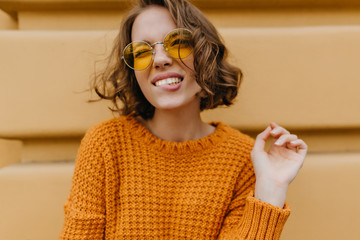 Glad girl with curly hairstyle enjoying time outdoor and posing with pleasure. Portrait of wonderful female model in yellow sunglasses and soft sweater making funny faces. Wall mural