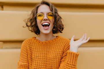 Enthusiastic smiling girl with shiny curls posing in front of old wall. Close-up outdoor portrait of enchanting lady in sweater and trendy glasses. Wall mural