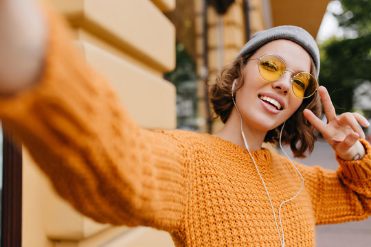 Attractive young woman in sport hat making selfie with peace sign during walk outdoor in cold day. Portrait of cheerful girl in bright knitted sweater having fun on the street.