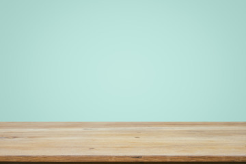 Empty wooden deck table over mint wallpaper background.
