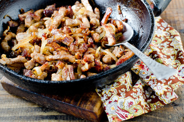 Meat fried with onions in a frying pan
