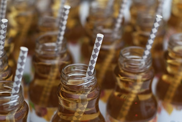 Glass Bottles with apple Juice with Straw on White Isolated Background
