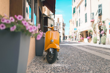 Foto op Plexiglas Scooter Vintage orange scooter standing in street of Alghero. Sardinia. Italy.