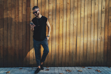 Handsome hipster guy wearing black blank t-shirt is sharing photos with friends via smartphone connected to 5G wireless internet while standing next to copy space area for your logo or design.
