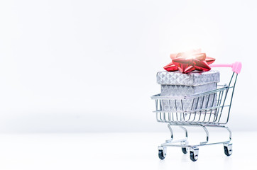 Shopping trolley with christmas gift. Gift box with red ribbon isolated on a white background. Christmas decoration.