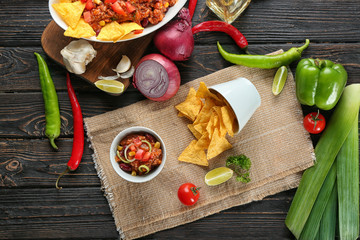 Bowl with chili con carne and nachos on table
