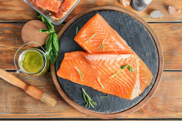 Fresh raw salmon fillet and marinade on wooden table