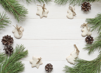 Christmas frame, decoration, fir tree and sugar-glaze cookies on white wooden table.