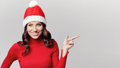 smiling beautiful girl in red christmas sweater and cap