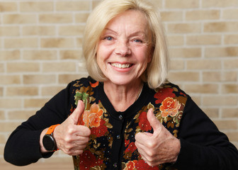 Happy smiling mature woman showing thumbs up gesture, brick wall background