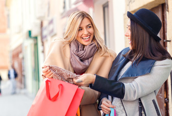 Two smiling young woman with shopping bag in the city on sunny autumn day.