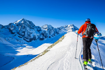 Mountaineer backcountry ski walk along a snowy ridge with skis in the backpack. In background blue sky and shiny sun and Ortler in South Tirol, Italy.