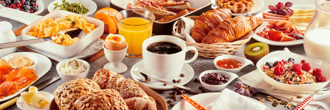 Breakfast with coffee surrounded by various food