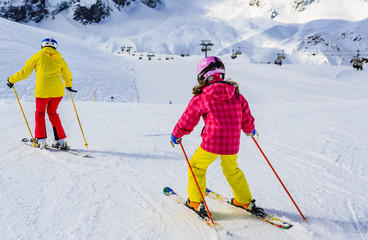 Fototapete - Woman skiing with daughter on snow on a sunny day in the mountains. Family ski in winter seasonon, the tops of snowy mountains in sunny day. South Tirol, Solda in Italy.