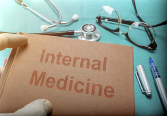Doctor Holds Book On Internal Medicine In A Hospital