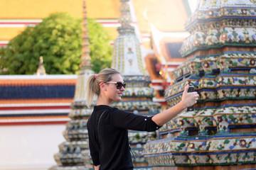 Woman tourist is selfie inside Wat Pho in Bangkok, Thailand.