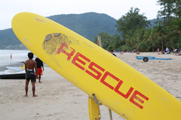 "A surf board with word ""RESCUE"" on beach."