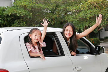 Mother and little child girl sitting on a car looking camera and waving goodbye. Holiday concept.