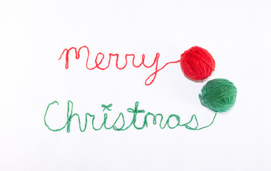 Merry Christmas Written in red and green yarn with Balls of Yarn on the Right. Photographed against a white background.