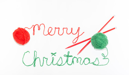 Merry Christmas Written in red and green Yarn with Crossed red Knitting Needles. Photographed against a white background.