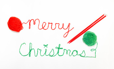 Merry Christmas Written in red and green yarn with red knitting Needles in Parallel. Photographed against a white background,.