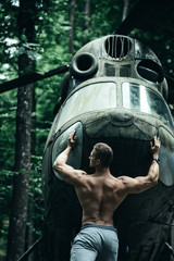 Man athlete with strong hands push helicopter