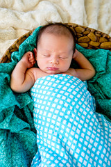 New Baby Boy in woven basket sleeping wrapped in  checked wrap